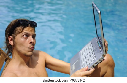 Man looks into his webcam while sitting poolside