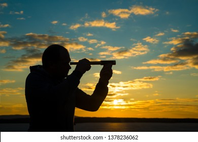 A man looks into a use monocular telescope against a dramatic sky at sunset. business concept idea, look to the future, look, spy. Businessman. Vision