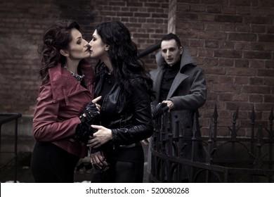 The man looks like two women kissing vampires