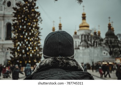 A man looks at main square with blurred cathedral and Christmas tree, holidays' spirit, street photography