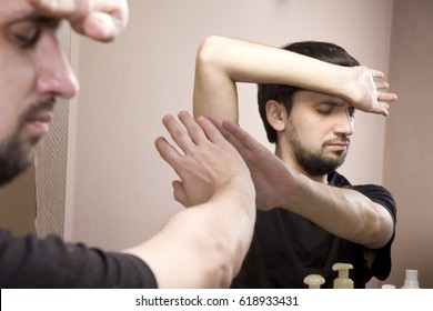 The man looks in the mirror. A man is worried about his appearance. Feeling of inferiority, complexes, low self-esteem. He covers his face with his hands