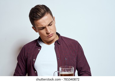 man looks at mug with beer on light background, alcohol