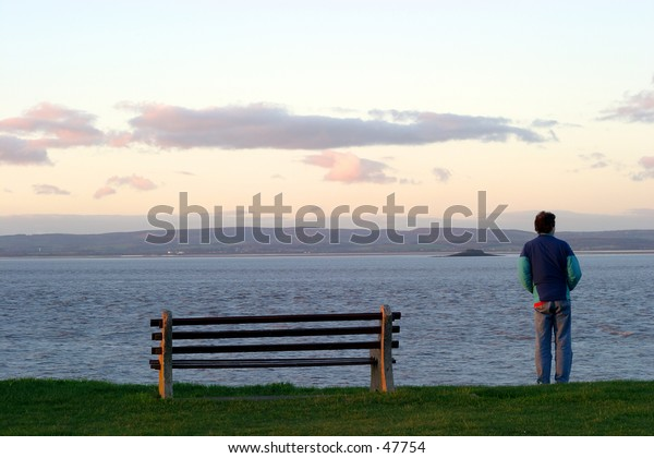 A man looks out over the river as the sun sets. The river is the River Severn (Severn Estuary) from Portishead, England. You can see Wales in the distance.