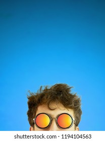 Man looks out. Person in sun glasses with disheveled hair on blue gradient background. Copy space for text. Crop 4x5 vertical