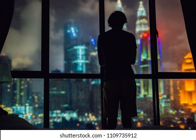 Man looks out the window at the night city.