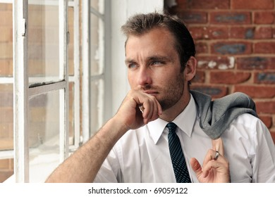 Man looks out the window thoughtfully, nice portrait of a businessman