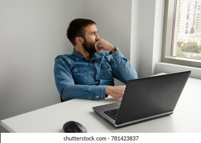 A man looks out of the window while working on a laptop