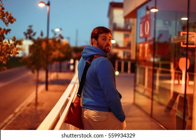 Man looks over his shoulder while walking before glass show-windows in the evening