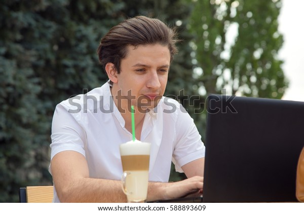 Man looks at the screen of his laptop, sitting at an outdoor cafe. Work in the open air.