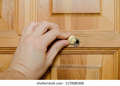 The man looks through the peephole in the door, hatch the eyelet in the wooden door. Looking who came, watching other people. The hand reveals a covered viewfinder in the door.