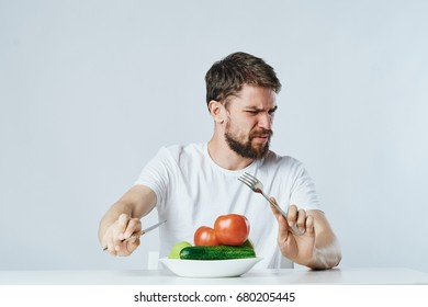 The man looks at the vegetables with disgust