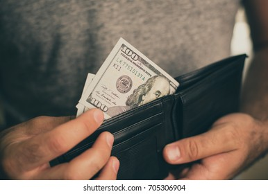 Man looks in the wallet. Cash. Wealthy man counting his money. Close up.