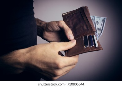 Man looks in the wallet. Cash. Wealthy man counting hi