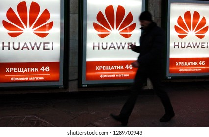 a man loooks on his a mobile phone walking past to Huawei logotypes, glowing light boxes with Huawei brand store advertising, with  in Kiev, Ukraine, 18 January 2019.