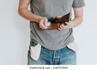 Man loose all the money to casino. In his leather wallet is empty no cash only have one chip left. Concept of unemployed and having bankruptcy gambling addicted no money, isolated on white background.