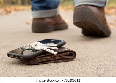 The man lost his keys, phone and wallet with money. Men leave and only the legs and shoes are not in focus and the keys, phone and wallet on the ground
