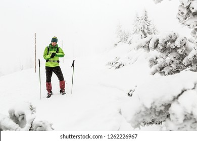 Man lost on winter trekking expedition in white snowy mountains with snow blizzard. Using GPS smart watch to find a way, adventure and expedition concept.