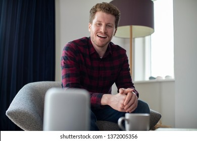 Man In  Lounge At Home Asking Digital Assistant Question