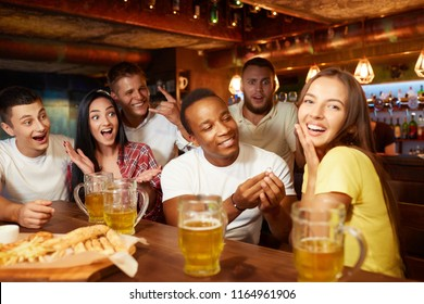 Man in love proposing surprised, shocked woman to marry in bar while gathering with friends. Boy holding wedding engagement ring, girl happy and smiling at camera, all around in shock and confusing.