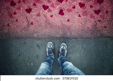 Man in love standing on textured grunge asphalt city street with red heart shapes, point of view perspective. Lovely valentine day conceptual background.