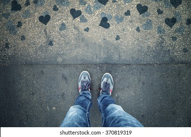 Man in love standing on textured grunge asphalt city street with blue heart shapes, point of view perspective. Lovely valentine day conceptual background.