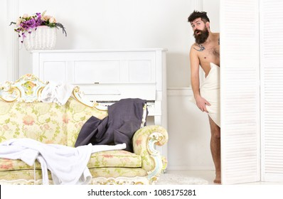Man, lover in white interior caught naked. Man with beard and mustache hiding behind folding screen. Hipster naked on shocked face unexpectedly detected in bedroom. Lovers and cheating concept.