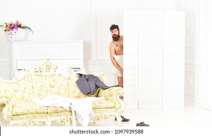 Man, lover in white interior caught naked. Lovers and cheating concept. Hipster naked on shocked face unexpectedly detected in bedroom. Man with beard and mustache hiding behind folding screen