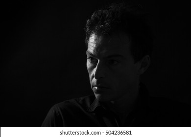 Man low key high-contrast portrait in backlight with a serious look on his face.