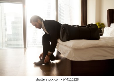 Man with luggage puts on shoes on hotel room bed. Young businessman getting ready to go on business trip. Entrepreneur preparing to travel in home bedroom in early morning. Business tourism, vacation