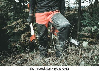 Man lumberjack with axe and chainsaw going to hard work in the wood Concept of hard work and sustainable economy