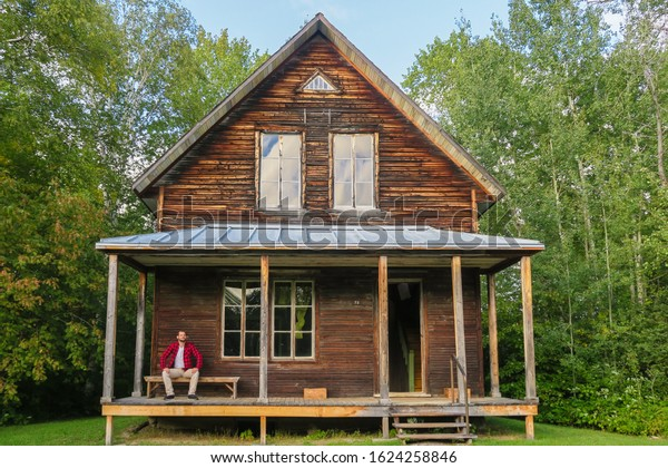 Man with a lumberjack shirt sitting on the front porch of a wooden house at Val-Jalbert historical village, Quebec, Canada