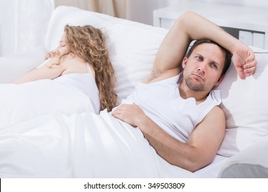 Man is lying in bed with girlfriend and thinking