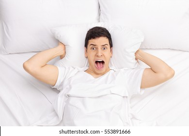 Man lying in bed and screaming