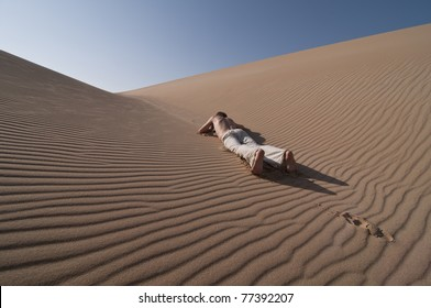 man lying between desert sand dunes
