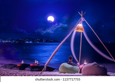 A man is lying down on bean bag on the beach in the evening with full moon.Koh Samui Thailand