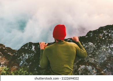 Man lying down on the edge cliff above clouds gaze into abyss mountains travel adventure lifestyle extreme vacations