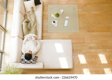 Man lying down on sofa in the living room