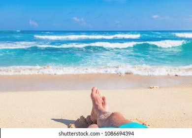 Man lying and enjoying on a sandy tropical beach.