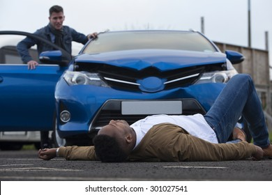 A man is lying in front of a damaged car which has just hit him. The responsible driver is standing at the door of the car, looking at him with a worried expression.