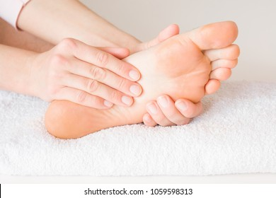 Man lying and getting treatment in health center. Masseur's hands doing massage on young, tired man's feet. Relaxing and resting day. Professional care service. Healthcare concept.