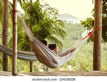 man lying in a hammock freelancer and running, beautiful mountain views, drinking wine