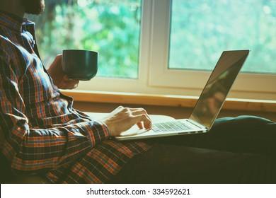 Mann, der auf einem Laptop liegt und Kaffee oder Tee trinkt