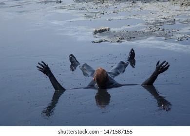 man lying in the mud
