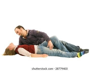 A man is lying near his girl. He looks at her while she is laughing.