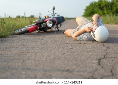 The man is lying on the asphalt near his motorcycle, the theme of road accidents