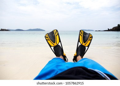 Man lying on the beach with yellow and black flippers fins on vacation