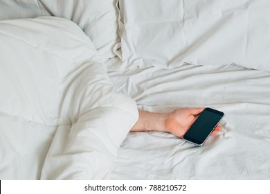Man lying on the bed and holding smartphone in hand