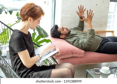 man lying on couch at psychotherapist emotionally discussing with psychotherapist at his problems, doctor making notes