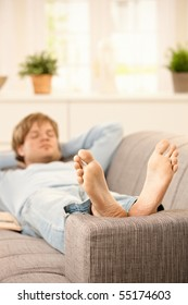 Man lying on couch relaxing with bare feet up at home in sunny living room.?