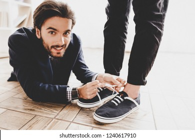 Man Lying on Floor and Tying Colleague's Shoelaces. Business Meeting in Office. April Fools Day. Businessman in Office. April Jokes. Holidays and Celebration Concepts. Jokes in Office.